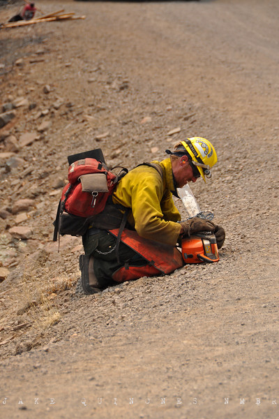 A wildland firefighter repairs and oils his chainsaw between bouts of underbrush clearing.-Hell Roaring Mesa, Catron County, NM